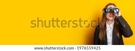 smiling young business woman looking through binoculars on yellow background. Royalty-Free Stock Photo #1976559425