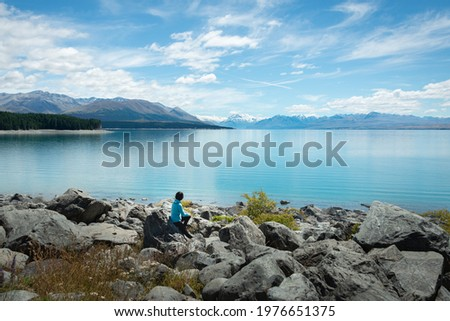 Woman sitting on the shore of Lake Pukaki, enjoying the views of Mt Cook and Southern Alps, South Island. Royalty-Free Stock Photo #1976651375