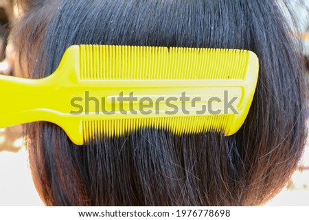 A louse comb on hair of child's head.