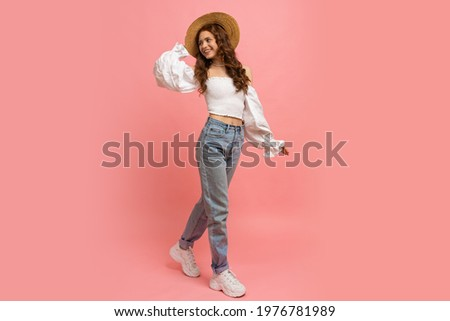 Full length image of Playful  woman in elegant linen top with balloon sleeves  and blue jeans posing on pink background.  Summer fashion trends.