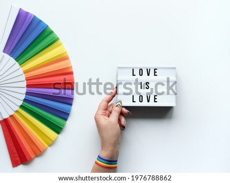 LGBTQ pride month decor. Text Love is Love on lightbox. Rainbow fan on white background. Human hand with rainbow nail varnish holds light box. June, LGBT pride month pride simple minimal decor.
