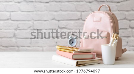 Female school backpack with stationery supplies on desk at white loft brick background. Elegant bag for carrying schooler accessories with notebook, pencil and sketchbook. Back to school concept Royalty-Free Stock Photo #1976794097
