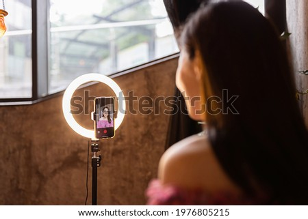 Young woman making photo or video content for social media with smartphone and light of ring lamp. Beauty blogger smiles to mobile phone screen. Influencer Makes broadcast communicates with followers Royalty-Free Stock Photo #1976805215