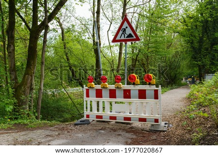 Red and white plastic portable barrier in front of a construction site. Red signal lights and road works sign.