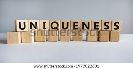 Inclusiveness and uniqueness symbol. Wooden cubes with the word 'uniqueness'. Beautiful white background. Business, inclusiveness and uniqueness concept. Copy space.