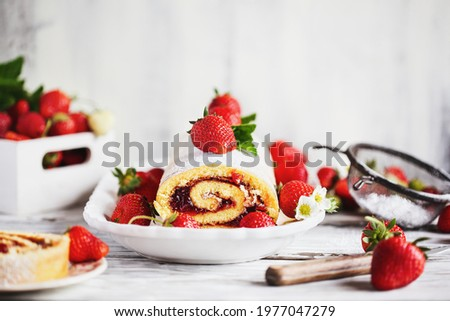 Homemade strawberry shortcake cake roll or Roulade with a berry jam filling and powdered sugar with mint leaves. Dessert over a white rustic table. Selective focus with blurred foreground  background