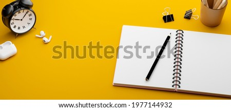 Yellow study table with stationery, clips, earphones and clock, 3D rendering, 3D illustration
