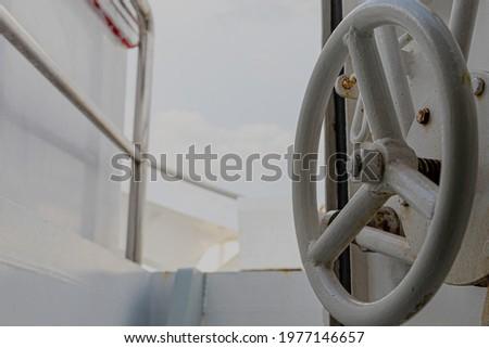 Iron wheel door handle open to boat deck. Door handle in round shape on a yacht or sailing boat