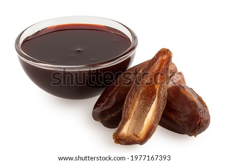Date syrup in a glass bowl next to whole and cut dry pitted dates isolated on white. Royalty-Free Stock Photo #1977167393