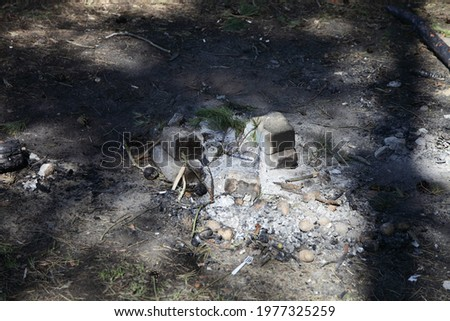 Gray ashes in abandoned extinguished fire place white bricks ring on ground close up with sun shadows, outdoors picnic leisure, empty campsite fireplace safety on a spring day, picture with copy space