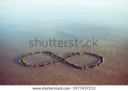 Minimal eternity and infinity symbol hand drawn on a sand