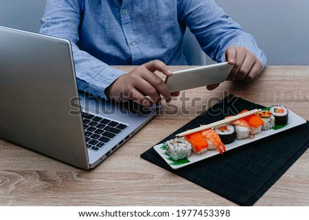 Boy taking a picture with his mobile phone of a plate of sushi on a black mat.
