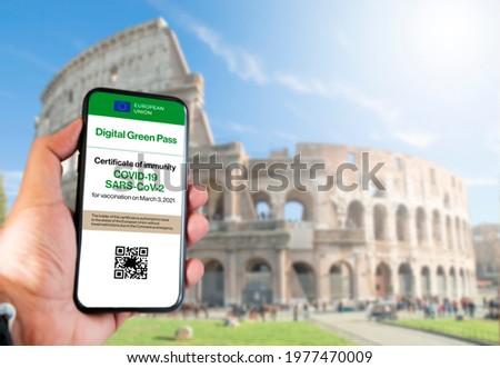 The digital green pass of the european union with the QR code on the screen of a mobile held by a hand with blurred colosseum in the background. Immunity from Covid-19. Travel without restrictions.
