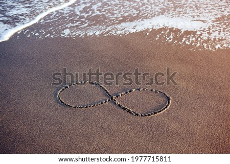 As old as the sea. The infinity symbol on wet sand as a metaphor of philosophical acceptance of the end.