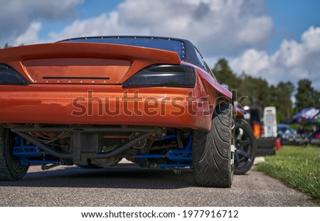 Power drifting car from side. back view Royalty-Free Stock Photo #1977916712