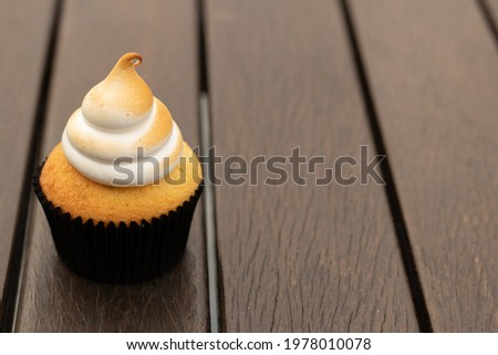 Small tasty cupcake on a dark ripped wooden table. Horizotal image with cupcake on the side leaving space for text. Blurred background.