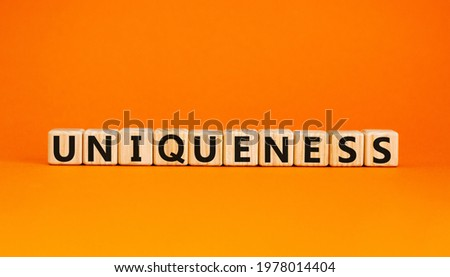 Inclusiveness and uniqueness symbol. Wooden cubes with the word 'uniqueness'. Beautiful orange background. Business, inclusiveness and uniqueness concept. Copy space.