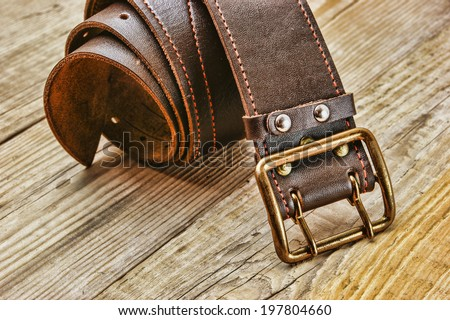 leather belt with a buckle on a wooden board Royalty-Free Stock Photo #197804660