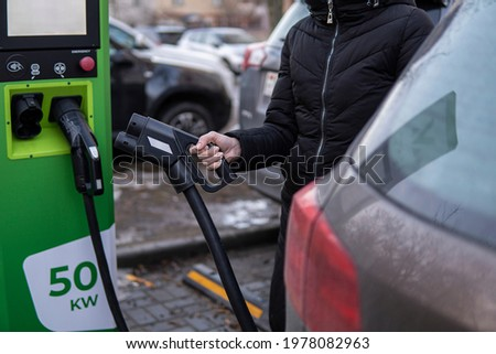 Girl to charge electric car. Hold in hand a cable to charge an electric car