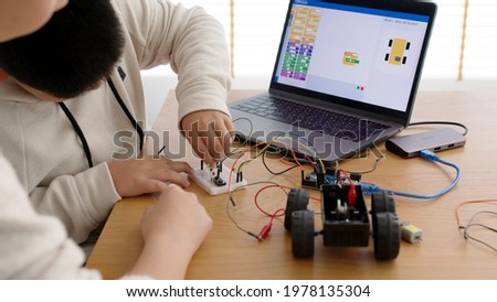Young asia student remotely learn online at home with parent in coding robot car and electronic board cable in STEM, STEAM, mathematics engineer science technology computer code in robotics for kids. Royalty-Free Stock Photo #1978135304