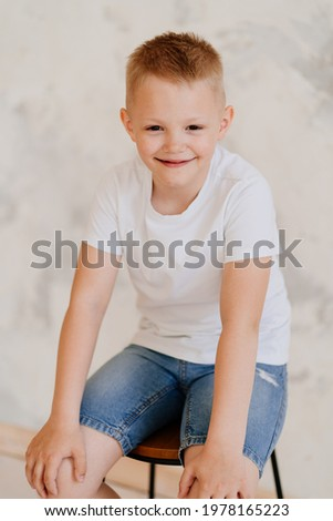 boy in a white T-shirt and denim shorts. psychological help waiting for teenagers. vitamins for the whole family. children's photo shoot for the school album.