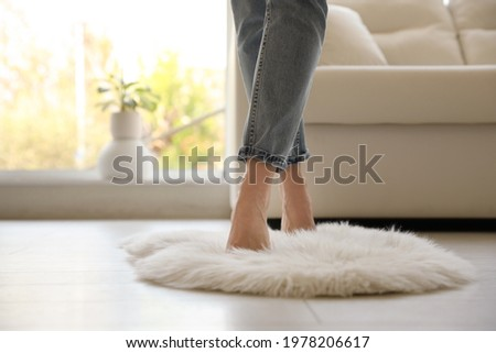 Woman standing on faux fur rug in living room, closeup. Space for text Royalty-Free Stock Photo #1978206617