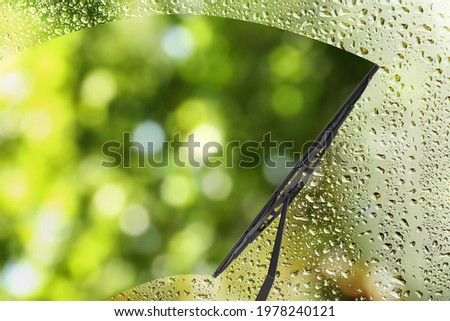 Car windshield wiper cleaning water drops from glass Royalty-Free Stock Photo #1978240121