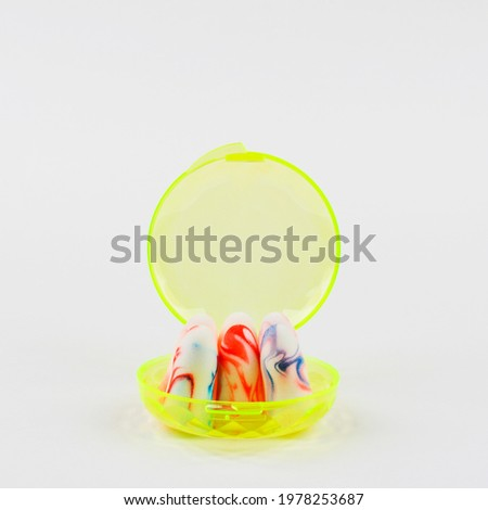 colorful earplugs in a yellow box on a white background