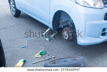 changing the car tire.Vehicle supported with a jack. wheelless vehicle supported by a jack