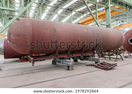 Manufacturing of the welded steel transportable pressure vessel constructed as a horizontal cylinder with domed ends. Royalty-Free Stock Photo #1978292864