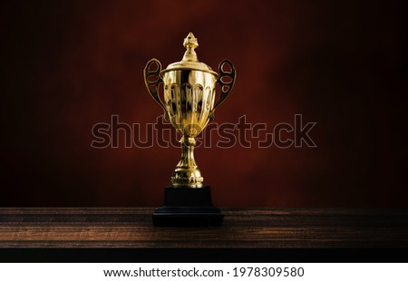 1st champion award, the best prize and winner concept, championship cup or winner trophy on wood table on black and dark brown wall background Royalty-Free Stock Photo #1978309580