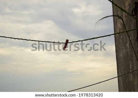 Clothes Clips Hanging on a Washing line Attached to Wall. Summer Evening Sky Background Royalty-Free Stock Photo #1978313420