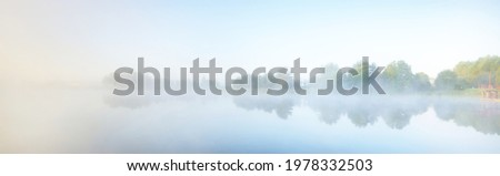 Lake shore in a fog at sunrise. Wooden pier close-up. Forest in the background. Symmetry reflections in the water. Idyllic rural scene. Atmospheric landscape. Ecological resort, fishing, swimming Royalty-Free Stock Photo #1978332503