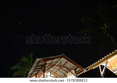 Scorpio constellation above a traditional hut on a beach in Malaysia at night.