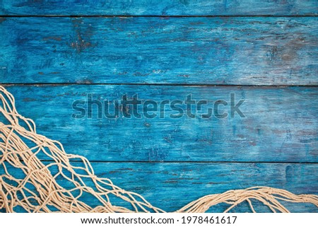 Fishing net on boho blue board background with copy space Royalty-Free Stock Photo #1978461617