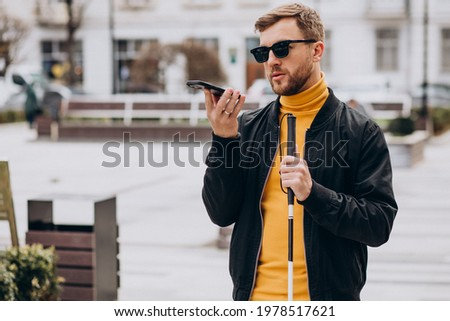 Young blinded man using phone and sending voice message Royalty-Free Stock Photo #1978517621