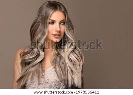 beautiful girl  hair coloring in ultra blond. Stylish hairstyle curls done in a beauty salon. Fashion, cosmetics and makeup. Royalty-Free Stock Photo #1978556411