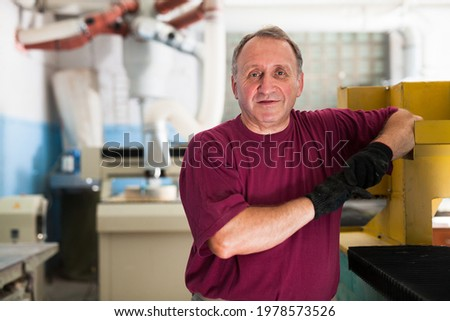 Portrait of elderly foreman in protective gloves standing in workshop. High quality photo