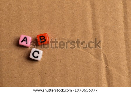 Selective focus with noise effect of colorful alphabet beads with text ABC.