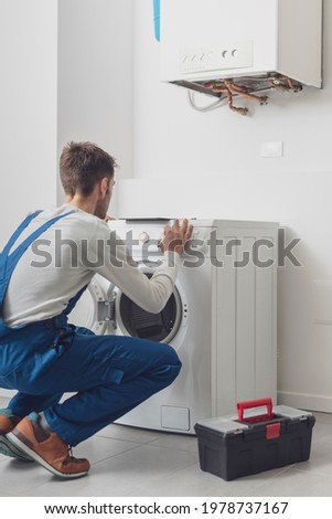 Repairman fixing a washing machine, he is adjusting a knob on the control panel Royalty-Free Stock Photo #1978737167
