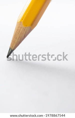 Pencil stands on white paper. The sharp point has just been sharpened. Focus on the black graphite tip. Vertical background image