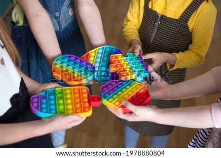children brought to kindergarten a popular toy pop it, hold in their hands anti-stress, silicone game Royalty-Free Stock Photo #1978880804