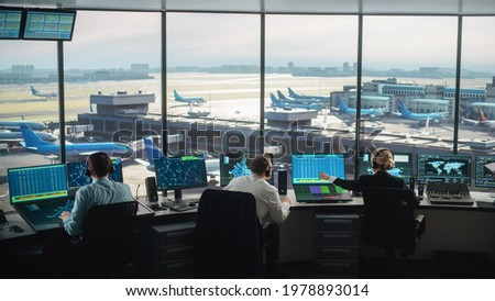 Diverse Air Traffic Control Team Working in a Modern Airport Tower. Office Room is Full of Desktop Computer Displays with Navigation Screens, Airplane Departure and Arrival Data for Controllers. Royalty-Free Stock Photo #1978893014