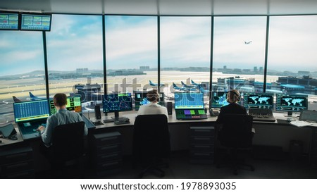 Diverse Air Traffic Control Team Working in a Modern Airport Tower. Office Room is Full of Desktop Computer Displays with Navigation Screens, Airplane Flight Radar Data for Controllers. Royalty-Free Stock Photo #1978893035