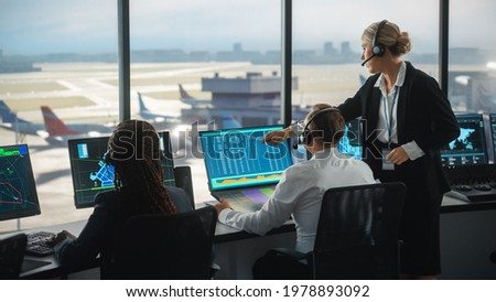 Female and Male Air Traffic Controllers with Headsets Talk in Airport Tower. Office Room is Full of Desktop Computer Displays with Navigation Screens, Airplane Departure and Arrival Data for the Team. Royalty-Free Stock Photo #1978893092