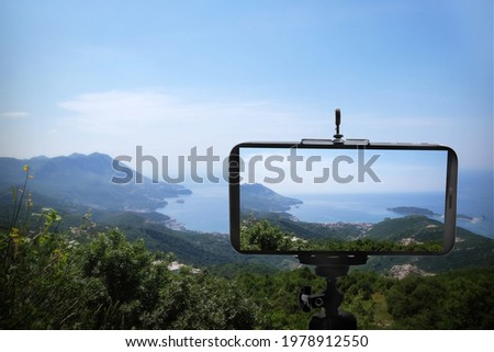 Taking photo of beautiful mountain landscape with smartphone mounted on tripod