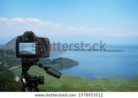 Taking photo of beautiful cove with camera mounted on tripod