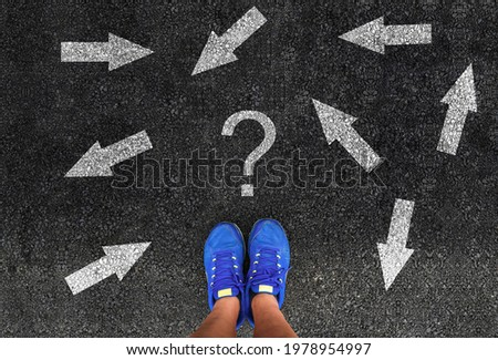 man in shoes standing on asphalt next to multitude of arrows in different directions and question mark, confusion choice chaos concept  Royalty-Free Stock Photo #1978954997