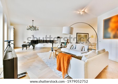 White sofas and tables on carpet against piano under chandelier in spacious living room decorated with art paintings