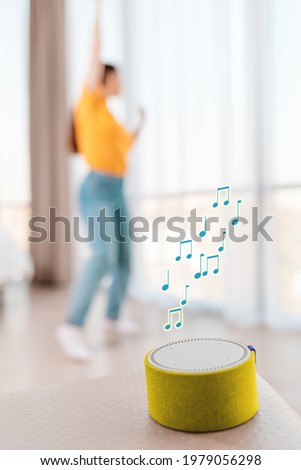 A portable smart yellow speaker plays music. Signs of melody. In the background, a woman dances in a blur. Vertical. The concept of modern gadgets.